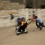 Palestinian boys play with a cart in the West Bank city of Ramallah, Sunday, May 3, 2009. (AP Photo/Muhammed Muheisen)