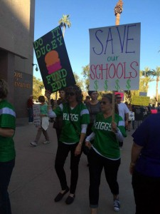 Two women march at a Phoenix protest in March against budget cuts for education. (Twitter/suerthjessica)
