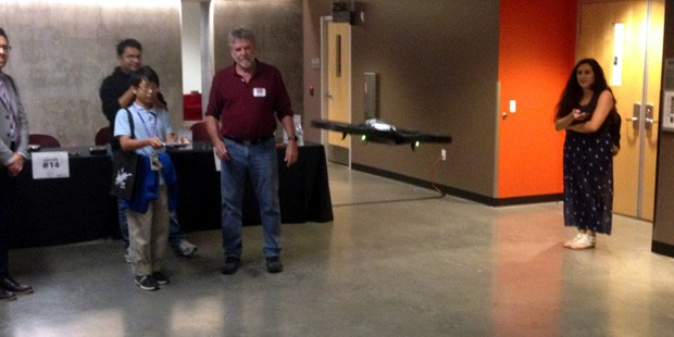 An exhibit visitor and Cronkite professor Steve Doig fly a drone on Cronkite's first annual Innovation Day. (KTAR Photo/Mike Sackley)