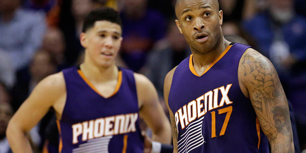 Phoenix Suns' P.J. Tucker (17) and Devin Booker (1) react to a foul call during the second half of the team's NBA basketball game against the Golden State Warriors, Wednesday, Feb. 10, 2016, in Phoenix. (AP Photo/Matt York)