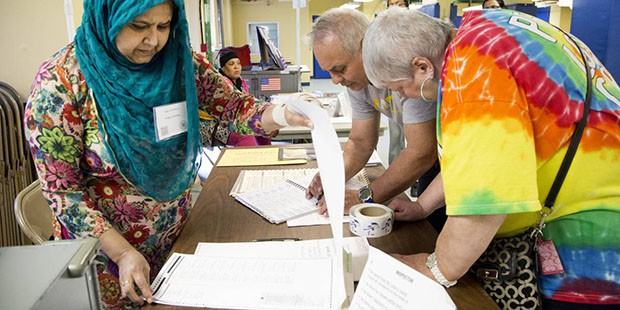 Poll worker Tahmina Banu, left, helps Edmund and Isabel Cruz sign in to vote, Tuesday, April 19, 2016, in the Flushing neighborhood in the Queens borough of New York. Banu is originally from Bangladesh. (AP Photo/Mark Lennihan)