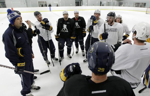 FILE - In this Jan. 8, 2013, file photo, former Buffalo Sabres player Andrew Peters, left, and Sabres players talk during an NHL hockey workout in Amherst, N.Y. Peters has been suspended indefinitely as coach of a youth hockey team pending a Buffalo police investigation into his role in an on-ice brawl. (AP Photo/David Duprey, File)