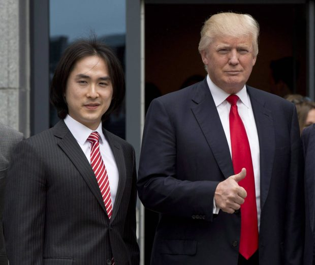 FILE - In this June 19, 2013, file photo, Donald Trump gives a thumbs-up as he poses with Tiah Joo Kim, left, CEO and president of Holborn Group, upon arrival to announce the building of Trump International Hotel and Tower Vancouver in downtown Vancouver, Canada. Malaysian property developer Tiah got way more than he bargained for when he signed a licensing deal to use the Trump brand on the Trump International Hotel and Tower that he is opening on Tuesday, Feb. 28, 2017 in Vancouver. (Jonathan Hayward/The Canadian Press via AP)