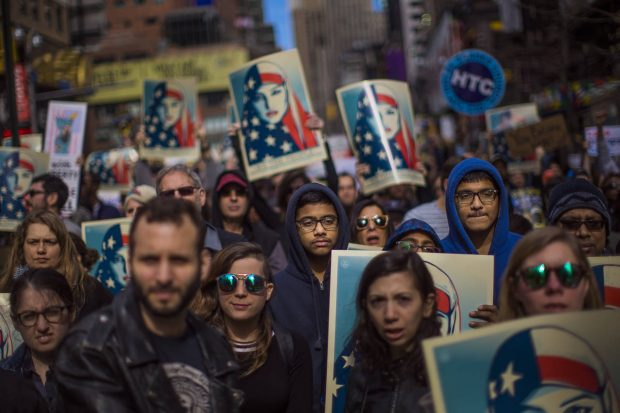 People carry posters during a rally in support of Muslim Americans and protest of President Donald Trump's immigration policies in Times Square, New York, Sunday, Feb. 19, 2017. (AP Photo/Andres Kudacki)