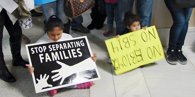 Children hold signs protesting an anti-sanctuary bill outside the House Education Committee meeting at the state Capitol in Little Rock, Ark., on Tuesday, Feb. 7, 2017. The panel rejected an effort to cut off state funding to colleges and universities that don't cooperate with federal immigration authorities. No state colleges have such a policy, but Republican Rep. Brandt Smith said he was trying to be proactive. Opponents said it could lead to profiling some students. (AP Photo/Kelly P. Kissel)