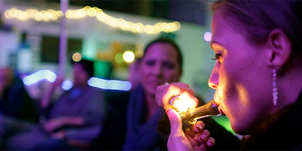 In this Dec. 31, 2012 file photo, Rachel Schaefer, of Denver, smokes marijuana on the official opening night of Club 64, a marijuana-specific social club, where a New Year's Eve party was held in Denver. (AP Photo/Brennan Linsley, File)