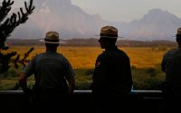 Park rangers stand talking together as the morning sun illuminates the Grand Tetons in Grand Teton National Park, north of Jackson Hole, Wyo., Friday, Aug 26, 2016. The National Park Service is celebrated its 100th birthday the day before. (AP Photo/Brennan Linsley)