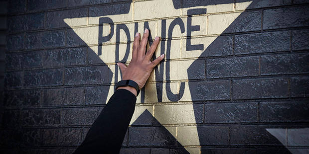 A fan touches the Prince star on the exterior of the building at First Avenue to remember him on the first anniversary of his death, Friday, April 21, 2017 in Minneapolis, Minn.  (Elizabeth Flores/Star Tribune via AP)