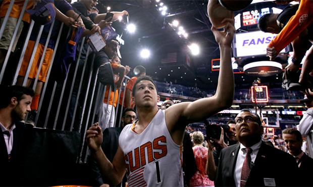 Phoenix Suns guard Devin Booker (1) hands an autographed shoe back to a fan as he walks off the cou...