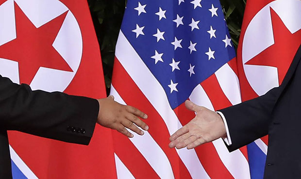 U.S. President Donald Trump, right, reaches to shakes hands with North Korea leader Kim Jong Un at ...