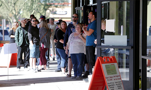 Voters wait in line to cast their ballots at a relocated polling station, Tuesday, Nov. 6, 2018 in ...