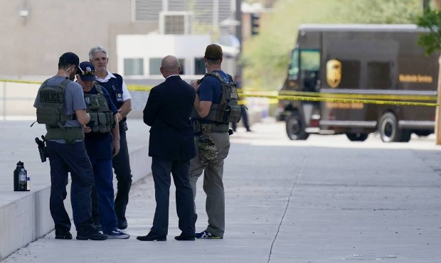 Federal law enforcement personnel stand outside the Sandra Day O'Connor Federal Courthouse Tuesday,...