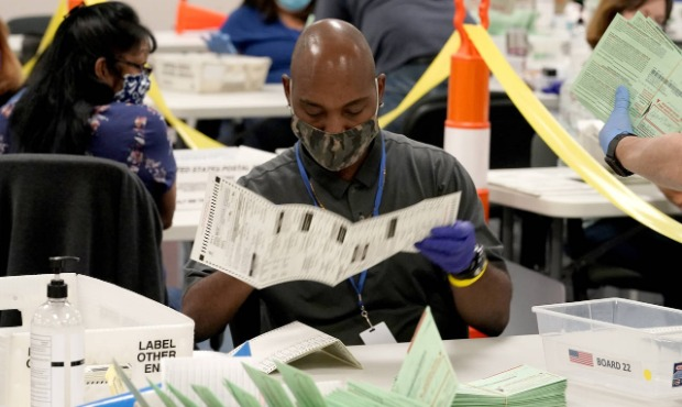 FILE - In this Oct. 21, 2020, file photo, election workers sort ballots at the Maricopa County Reco...