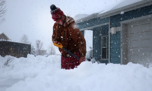 Tim Ahlman shovels snow outside his home in Bellemont, Ariz. Monday, Jan. 25, 2021. A series of win...