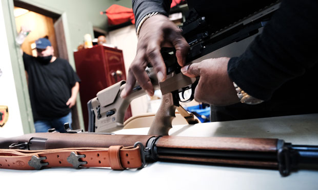 Lateif Dickerson handles some of his rifles at his gun instruction headquarters on March 25, 2021 i...