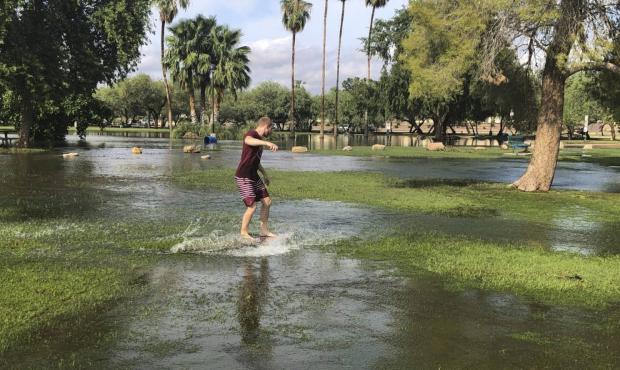 A man rides a boogie board in a flooded park in Scottsdale, Ariz., on Saturday, July 24, 2021. Heav...