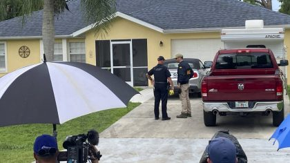 Law enforcement officials investigate home of a young man wanted for questioning in the disappearan...