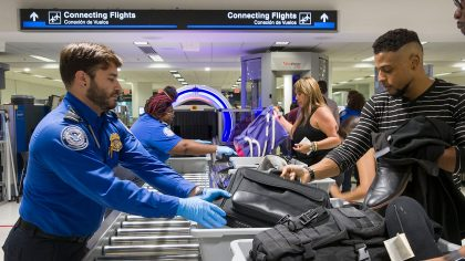 Transportation Security Administration (TSA) agents help travelers place their bags through the 3-D...